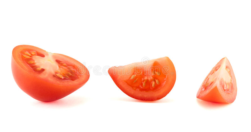 Fresh red tomato cut into pieces, isolated. Over white background stock image