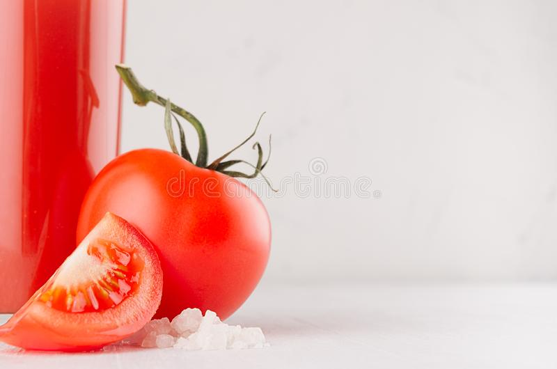 Fresh red tomato drink and pulpy tomatoes with juicy piece, straw, salt on light soft white wood table, copy space, closeup. stock photos