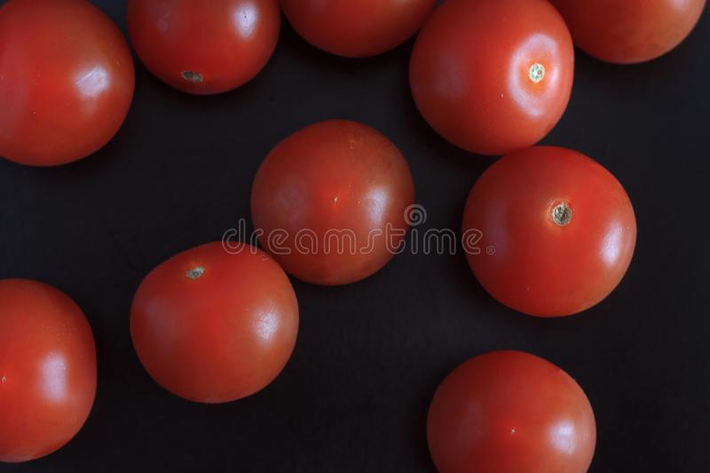 Fresh red tomatoes close up on black background royalty free stock photography