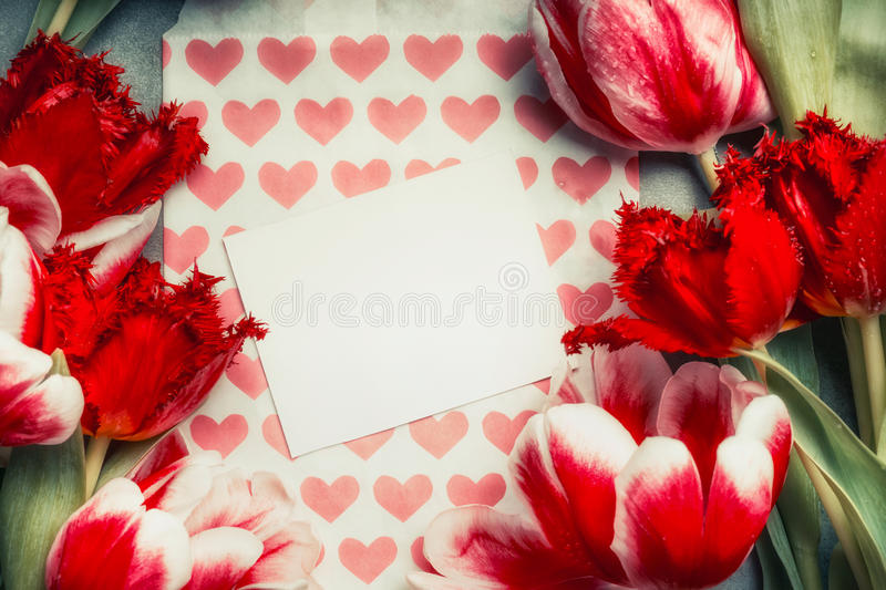 Fresh red tulips and blank greeting card with heart, top view, frame. stock photos