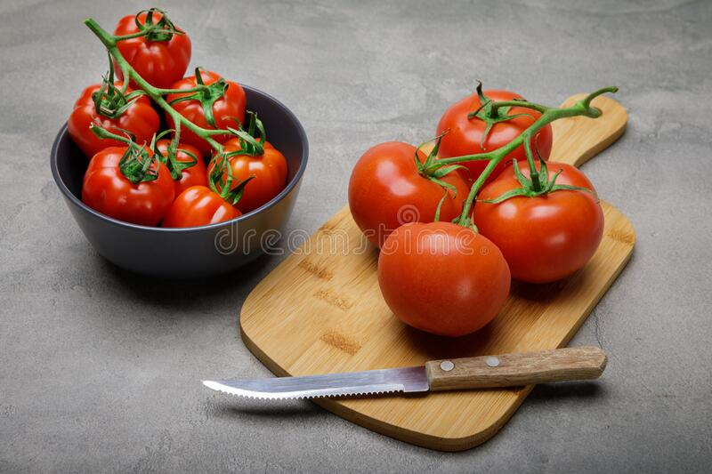 Fresh red variety of tomatoes on concrete rustic table. Tomato vegetable concept stock image