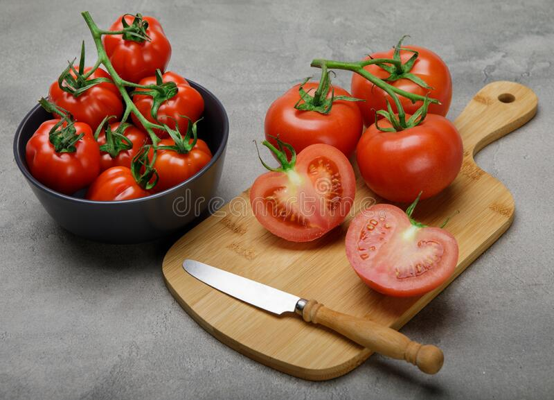 Fresh red variety of tomatoes on concrete rustic table. Tomato vegetable concept stock photo