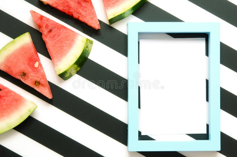 Fresh red watermelon slice on striped background with frame. Summer concept. Top view, Flat lay. stock photo