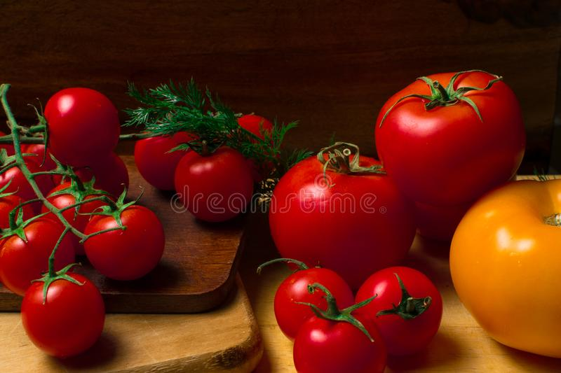 Fresh red and yellow tomatoes. With dill on wood background royalty free stock photos