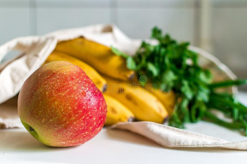 Fresh ripe apple, bunch of parsley and green onion, bananas and French baguette in canvas reusable grocery tote bag on the kitchen. Table. Spring purchases at stock images