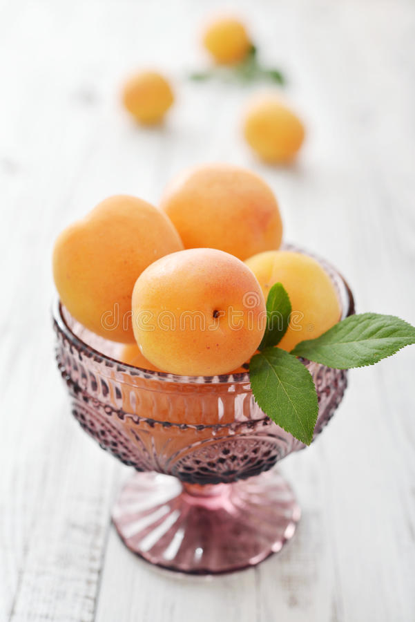 Fresh ripe apricots. In glass ramekin on wooden background stock images