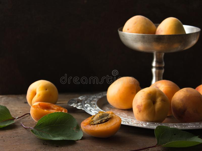 Various Fresh ripe apricots on wooden surface leaves fruits apricots on board cut apricots in half. Light blue rustic wood backgro stock photography