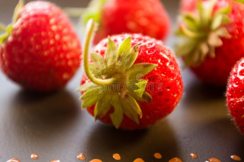 Fresh ripe berries strawberries on black ceramic plate, close up. Fresh ripe berries strawberries on black ceramic plate royalty free stock images