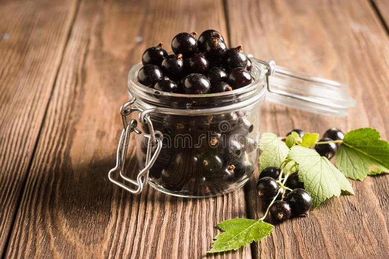 Fresh ripe black currant berry in a glass jar on a wooden background. Horizontal frame. royalty free stock images