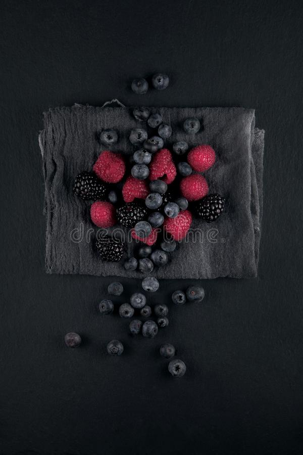 Fresh ripe blueberries, blackberries and raspberries on a napkin and slate plate kitchen table royalty free stock photo