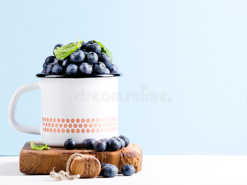 Fresh ripe blueberries in country style enamel mug on rustic wooden board over blue pastel background stock images