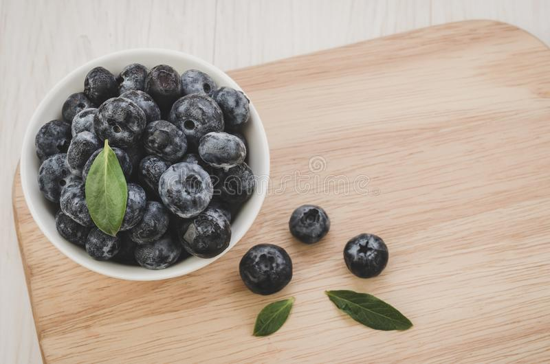 Fresh ripe blueberries with leaves in bowl/Fresh ripe blueberries with leaves in bowl on wooden tray. Copy space. Top view stock photography