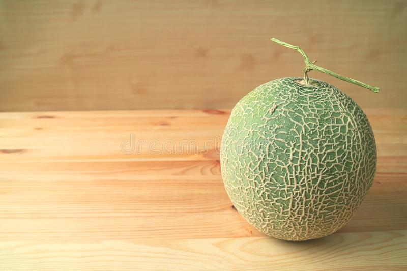 Fresh Ripe Cantaloupe Melon or Muskmelon Whole Fruit with Stem Isolated on Wooden Table stock photography