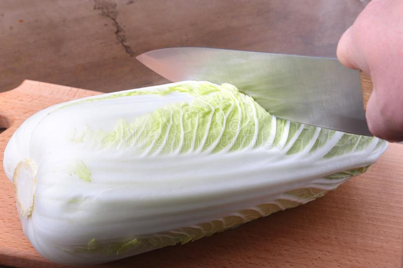 Fresh ripe Chinese cabbage and knife on the cutting board. Ingredients for salad. Ready for cooking. royalty free stock photo