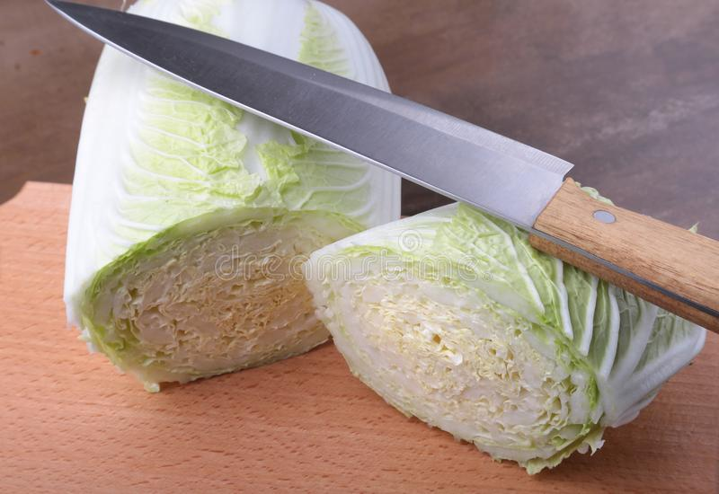 Fresh ripe Chinese cabbage and knife on the cutting board. Ingredients for salad. Ready for cooking. royalty free stock images