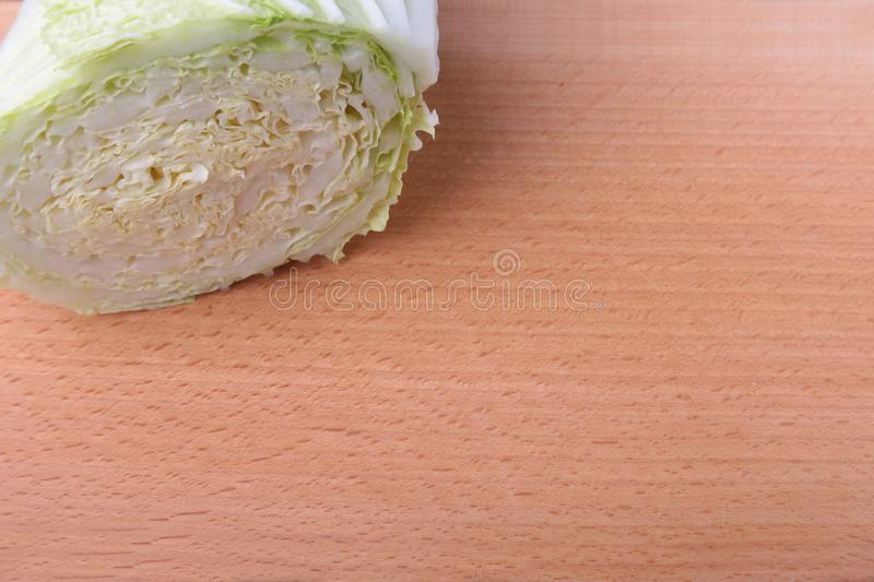 Fresh ripe Chinese cabbage and knife on the cutting board. Ingredients for salad. Ready for cooking. Close-up. stock photo