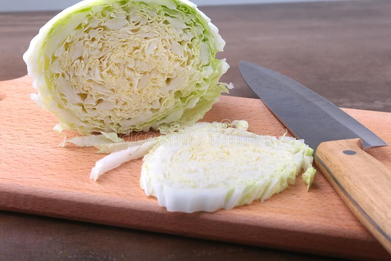 Fresh ripe Chinese cabbage and knife on the cutting board. Ingredients for salad. Ready for cooking. Close-up. royalty free stock photo