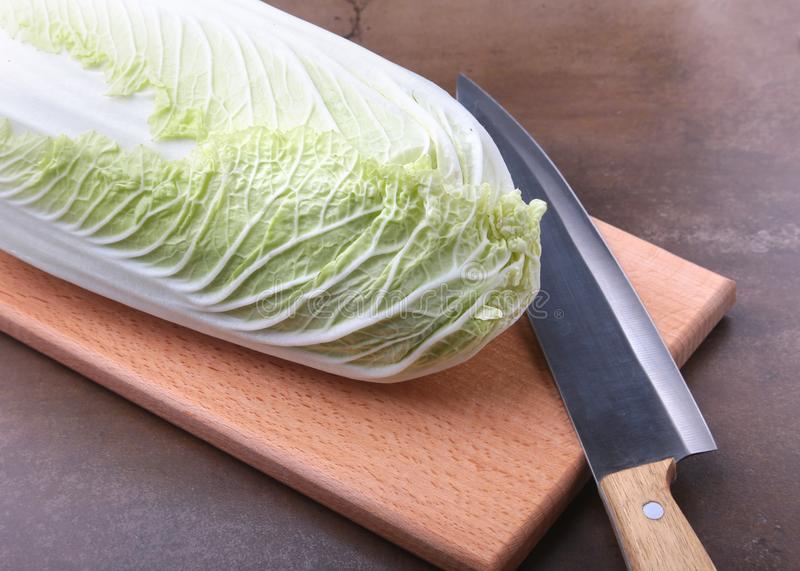 Fresh ripe Chinese cabbage and knife on the cutting board. Ingredients for salad. Ready for cooking. stock image