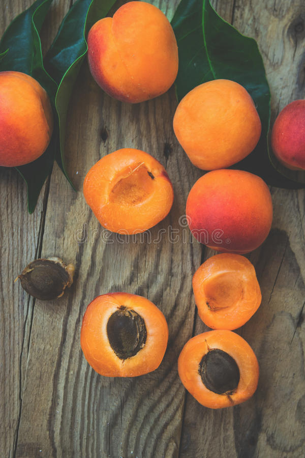 Fresh ripe colorful apricots halved and whole on weathered plank wood background, kernel, green leaves matte filter. Fresh ripe colorful apricots halved and royalty free stock image