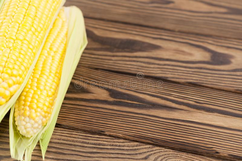 Fresh ripe corn in green leaf. On old rural wooden planks royalty free stock image