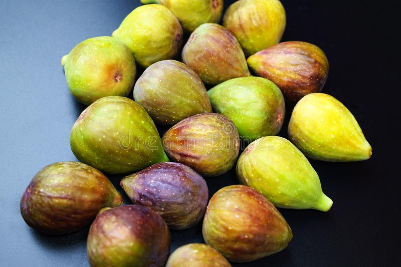 Fresh ripe figs on black background. royalty free stock photography
