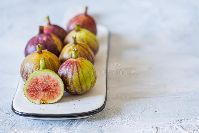 Fresh ripe figs on grey marble plate stock image