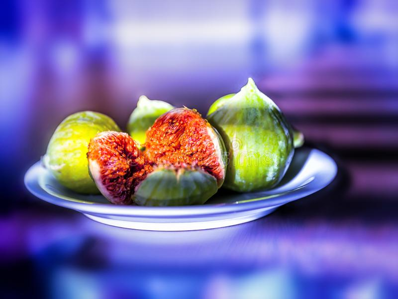 Fresh ripe figs on a plate on bright purple neon background stock photography