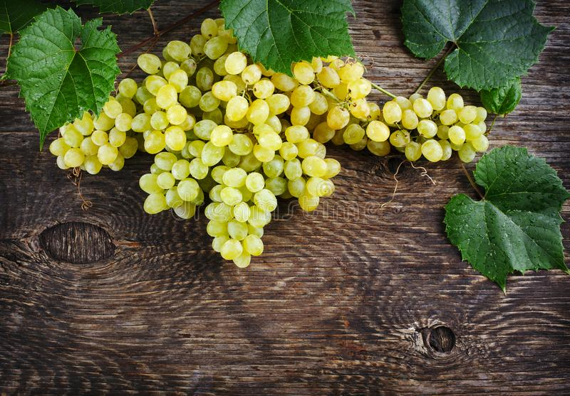 Fresh ripe grapes with leaves on a wooden background stock photo