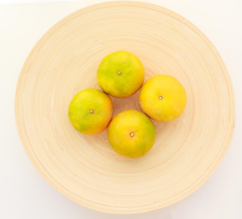 Fresh ripe green and orange tangerine citrus, mandarin oranges, fruit on wood tray isolated on white table background. Seasonal royalty free stock photo