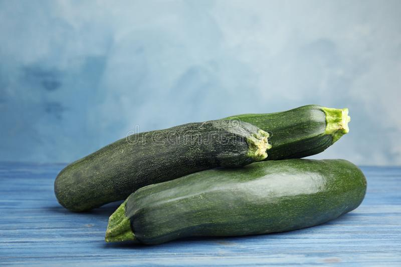 Fresh ripe green zucchinis on wooden table against blue background. Space for text royalty free stock image