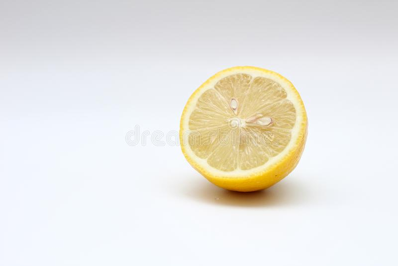 Fresh, ripe, isolated, juicy bisected lemon on a white background. Studio macro shoot royalty free stock image