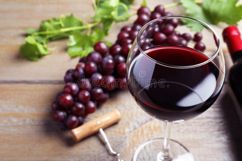 Fresh ripe juicy grapes and glass of  on wooden table, closeup royalty free stock photography