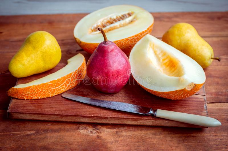 Fresh ripe juicy melon slices and pears on the table royalty free stock photography