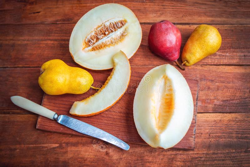 Fresh ripe juicy melon slices and plums on the table stock photo