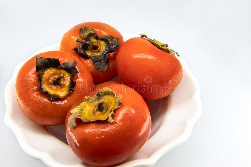 A pot of several red persimmons, fresh and ripe. stock photography