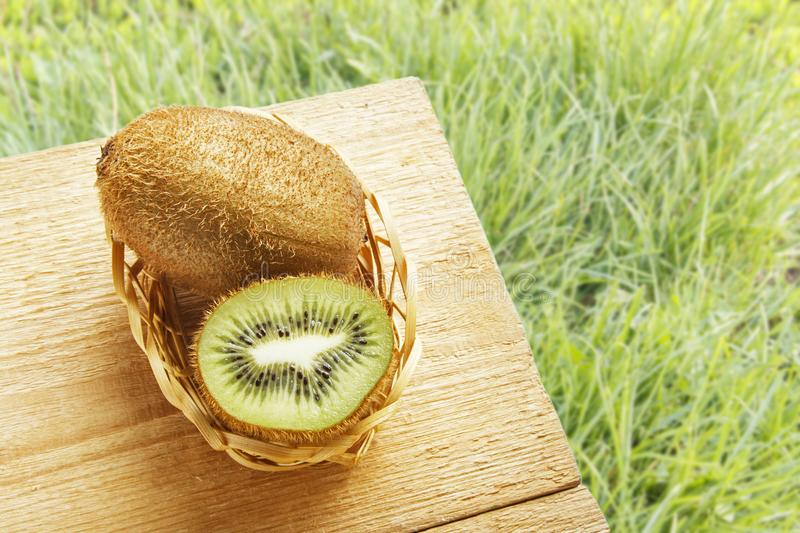 Fresh ripe kiwi fruit on wooden table and on green grasses background. Natural organic ripe fruits. Top view with copy space.  stock photography