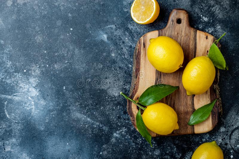 Fresh ripe lemons with leaves on wooden board over black stone background. stock photography