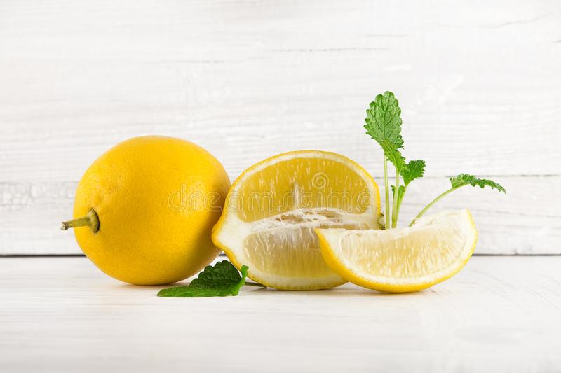 Fresh ripe lemons, slices, rustic food photography on white wood plate kitchen table royalty free stock image