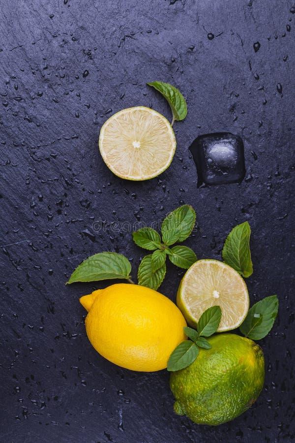 Fresh ripe limes with mint on black slate stone background. stock image