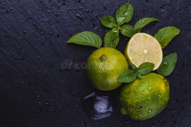 Fresh ripe limes with mint on black slate stone background. stock images