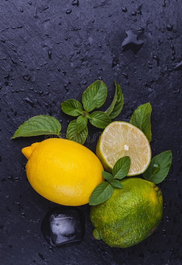 Fresh ripe limes with mint on black slate stone background. royalty free stock photography