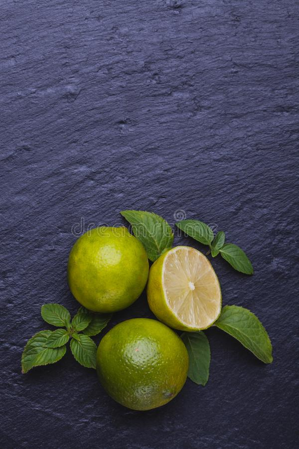 Fresh ripe limes with mint on black slate stone background. stock photography