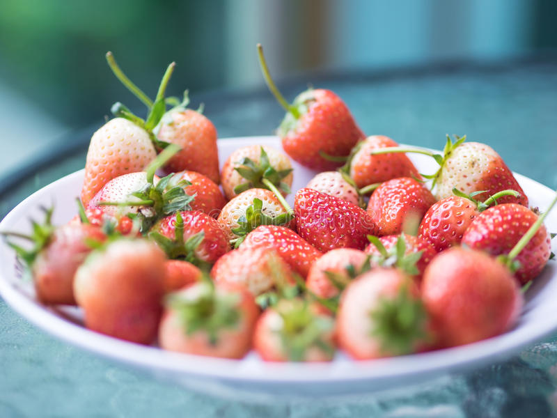 Fresh ripe natural strawberry, red and white fruit on glass table royalty free stock photos