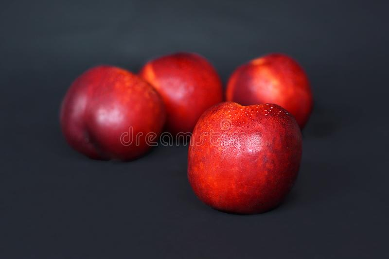 Fresh ripe Nectarine in front of blurry fruits on black background stock photos