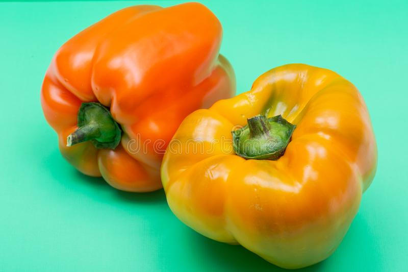 Fresh Ripe Organic Bell Peppers, a cultivar group of the species Capsicum annuum, isolated on green. Background royalty free stock photos
