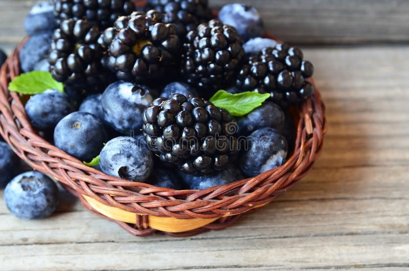 Fresh ripe organic blackberries and blueberries in a basket on old wooden table.Healthy eating,vegan food or diet concept.Selectiv royalty free stock image