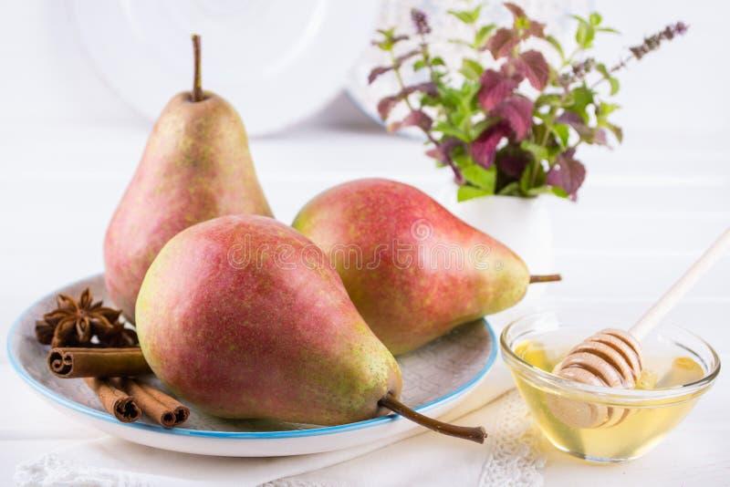Fresh, ripe organic sweet pears in dish with cinnamon sticks, anise stars and honey stock photos