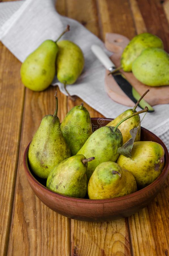 Fresh ripe pears in a clay bowl on a dark wooden background. royalty free stock photos