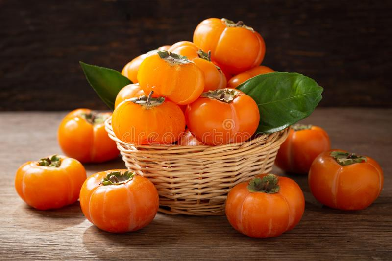 Fresh ripe persimmon fruit in a basket royalty free stock photo