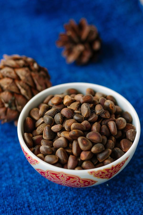 Fresh and ripe pine or cedar nuts in a bowl over blue background. stock photo